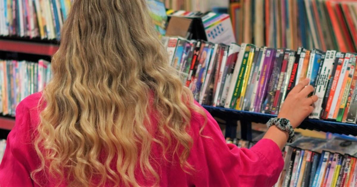 Femme qui magasine des DVDs chez Entraide Agapè